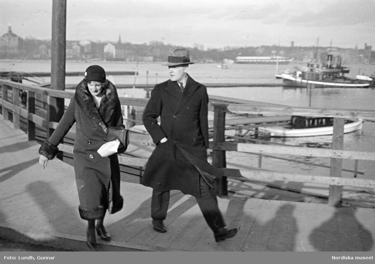 Slussen, Stockholm. Gångtrafikanter. En man och en kvinna på väg över gatan. I bakgrunden båtar på Saltsjön.