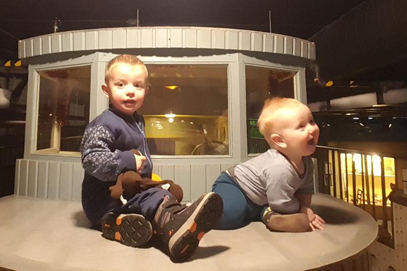 To små gutter sitter på dekket av lekebåten Queen of Congo i utstillinga Sally Jones.