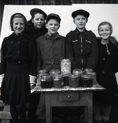 En grupp barn står stolta bakom en bord fullt med glasburkar med inlagda grönsaker. Unga Odlare 1948 - 1949.
