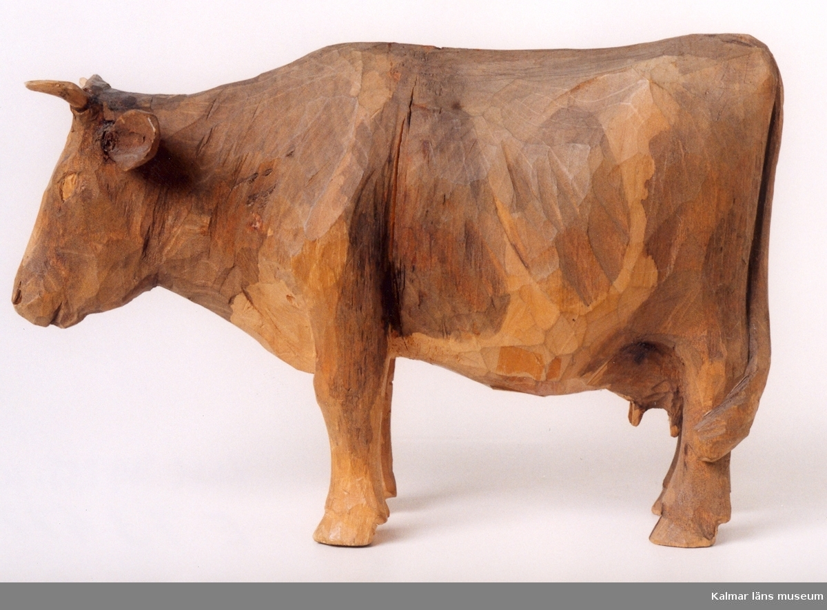 KLM 39255:10. Skulptur, av trä, bemålad ko. Signerad H.C. I blyerts på högra bakdelen. Under höger fram- och bakklöv påskrift: 18.
