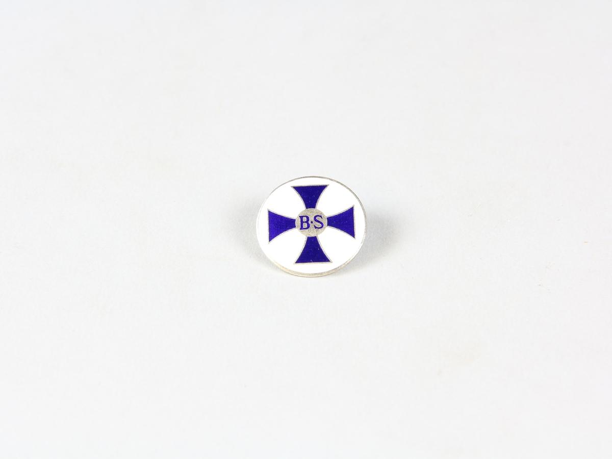 """Brosch till uniform för barnmorska. Rund, lätt kupig brosch av vitmetall. Framsidan med barnmorskornas emblem; ett blått mantuanskt kors på vit botten. I mitten en silverfärgad cirkel med bokstäverna """"BS"""". På baksidan en öppningsbar nål."""