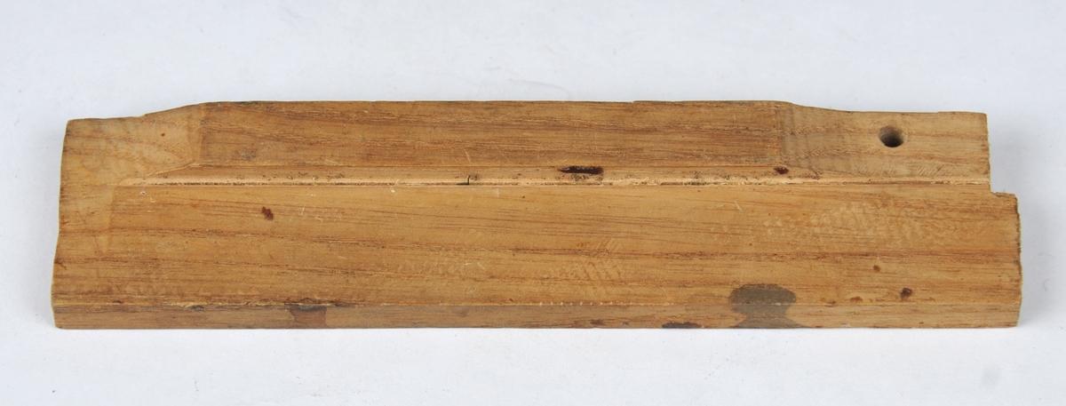 Rektangulær treplate med spor i lengderetningen. I den eine enden er det bora ut eit lite hol. Bruken er uviss.