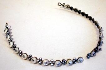 Bågformigt diadem av metall, besatt med små pärlemorrundlar med metallknopp. Mellan varje pärlemorrundel sitter grupper av metallknoppar. Diademet avslutas med öglor.