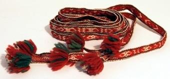 Mönstervävt band med plockat mönster. Bandet är vävt av vitt bomullsgarn med mönstertrådar av grönt och rött ullgarn. Avslutas i båda ändar med tre tofsar.