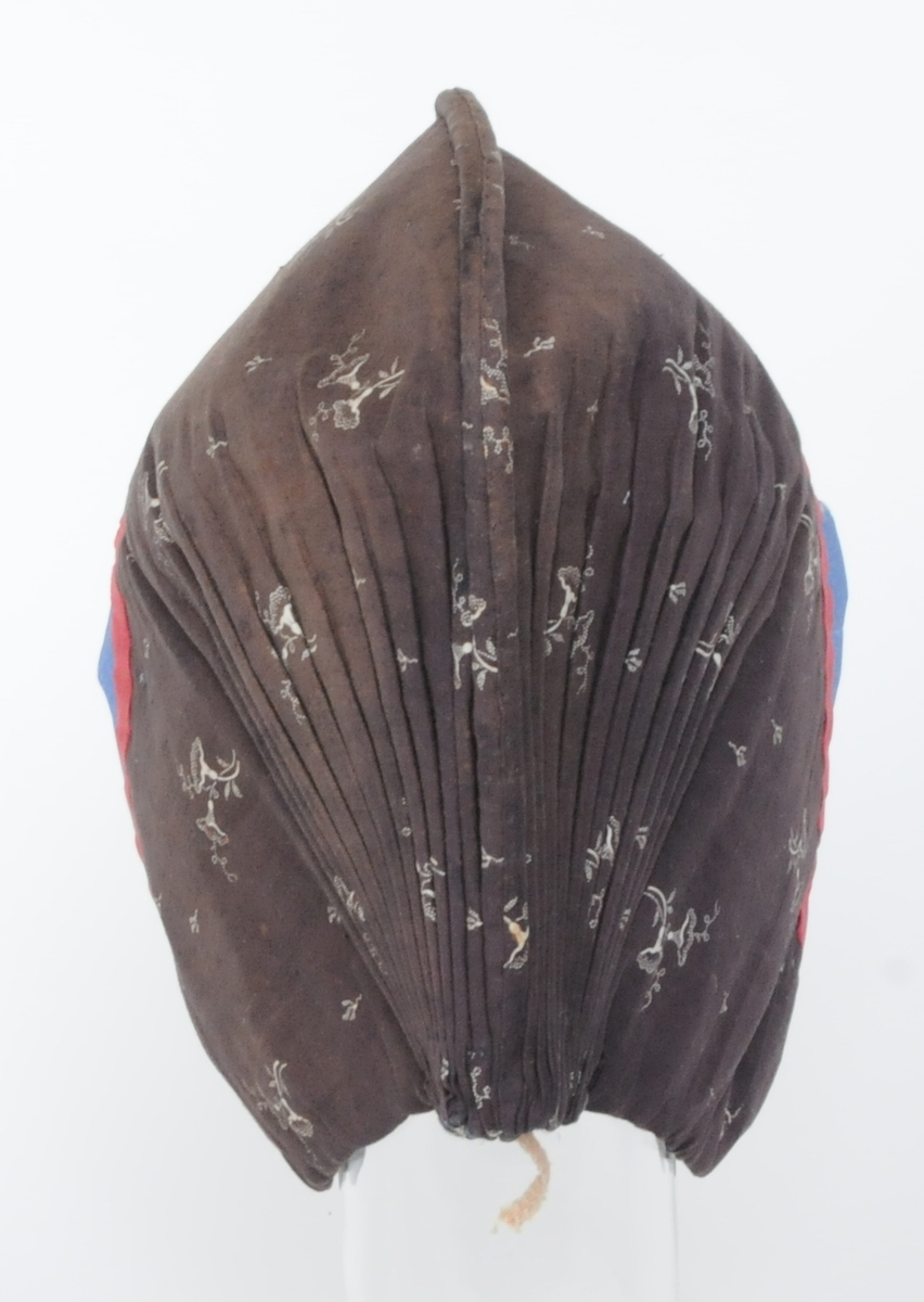 Mössa för kvinna, med vita blommor på brun botten och röda kantband.