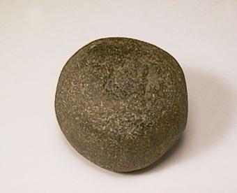 Glättsten av grå bergart. Närmast rund med släta ytor på två motsatta, flata sidor. Ytan är i övrigt är skrovlig men utan spår av slag. Tolkningen osäker, kan också vara en löpare till handkvarn.