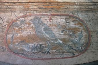 Blåmarmorerat skrivschatull med snedklaff som dekorerats med en medaljong med en skata i. Inuti är schatullet vitmålat och dekorerat med blommor och en basunängel. Fack för sex skjutlådor varav tre finns kvar, nummer 2, 4 och 6.