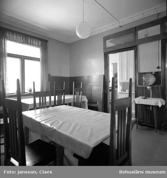 """Enligt uppgift: """"Matsalen i 2:a plan. Över dörrarna i matsalen finns målningar av Fanny Pettersson, dotter till Otto Pettersson, med motiv från bl a Kålhuvud, Kyrkesund och Marstrand. Ett motiv är från Holma vid Gullmarn. Det ursprungliga matsalsbordet syns längst bort i bild. Väggfasta bänkar och de ursprungliga matsalsstolarna. Träpanel. Inredning i mörkgrön bets. Till matsalsinredningen hörde även ett mörkgrönt betsat skåp som nu står i köket. Dörren leder till serveringsgång och där bakom kök""""."""