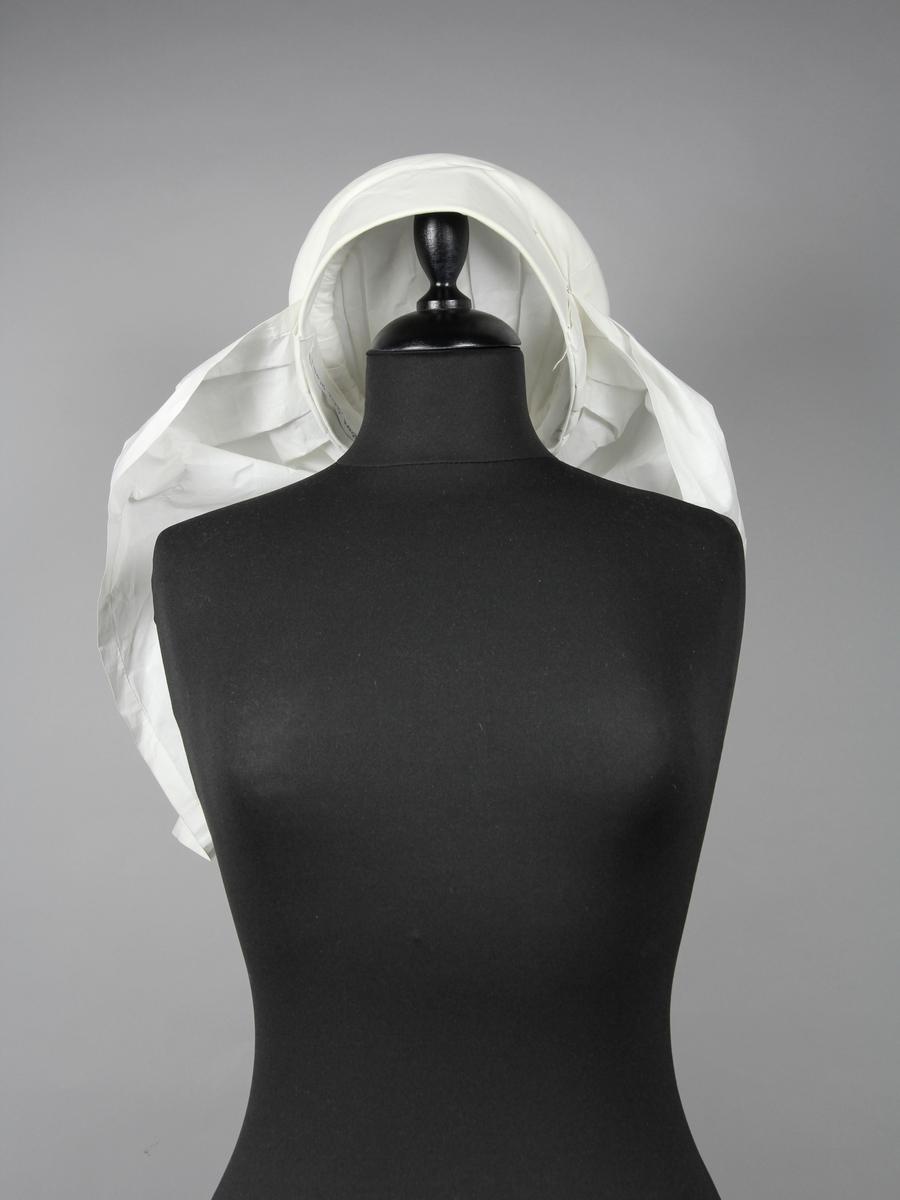 Klut till kvinnodräkten från Torna-Bara i Skåne. Utförd i tunnt stärkt linne. Tillverkad genom att ett tygstycke monterats i många veck och vridningar på en stomme av tyg och papper med en krans av rullat tyg överst. Duken är fästad i nacken som ett släp ner över ryggen. Mitt över ryggen är en dekoration i form av en blomma broderat i vitt med hålsömsbroderi.