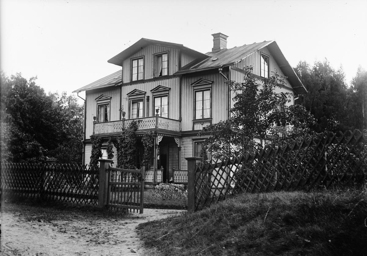 Bostadshus i trädgård omgärdat med staket, sannolikt i Sverige