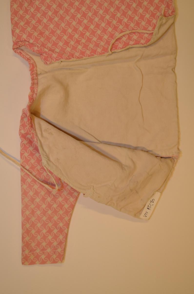 Spebarns-trøye i kvit bomullsflanell med trykt blomstermønster i rosa, fóra med kvit bomull. Opning i ryggen med to sett knyteband. Smal linning rundt halsen. Maskinsydd, kasta over med hand. Klypt i eitt stykke.