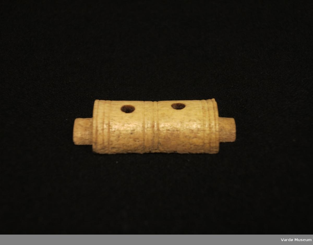 Halvsylindriske gjenstand med to hull. Gjenstand er en tredjedel av hele vabeinrullen.