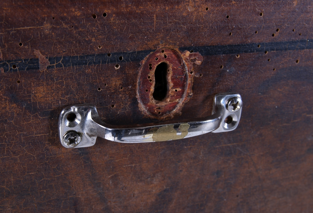 Ådret kommode på fotstykke hvor midtpartiet er utskjært i buet form. Profilert kant langs topplaten. Fire langskuffer, hvor skuffene i midten er rammet inn med to svarte søyler. Håndtak og nøkkelskilt i hver skuff.  Øverste skuff er inndelt i tre mindre rom og nøkkelen står i nøkkelhullet.