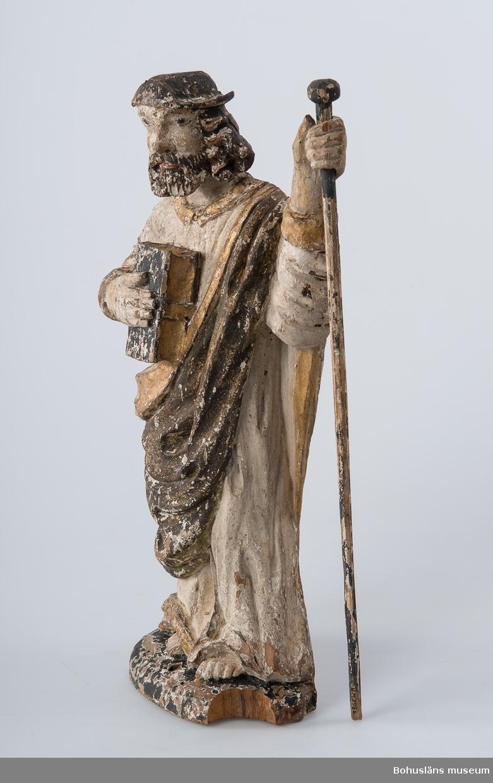 Träskulptur, apostelbild från 1600-talet som tilhör altartavla UM000393.  Förgyllningen som uppvisar båda bladguld, slagmetall och/eller silver. UM000395a = själva skulpturen,  UM000395b = skulpturens lösa stav.  Enligt katalogkort föreställer skulpturen helgonet och aposteln Jakob den äldre; tillhör altaruppsats UM000393a-i. Vandringsstaven brukar attribueras till Jakob den äldre. Krederat trä med mager oljefärg och oljeförgyllning.   Ur handskrivna katalogen 1957-1958: Apostelbild, Lane Ryr H. 39 cm; höger hand håller en bok, vänster en stav b) L. 39,5 cm. Färgen delvis flagn.; små bitar avslag.  Lappkatalog: 13  Se foto på föremålet i Uddevalla museums kyrkliga utställning 1920, UMFA53292:0013  Ur Nationalencyklopedin, NE.se:  Apostel I konsten framställs apostlarna alltid barfota samt klädda i tunika och mantel. De bär oftast en bok samt sitt individuella attribut, i allmänhet respektive martyrredskap (Petrus bär dock himmelrikets nycklar).