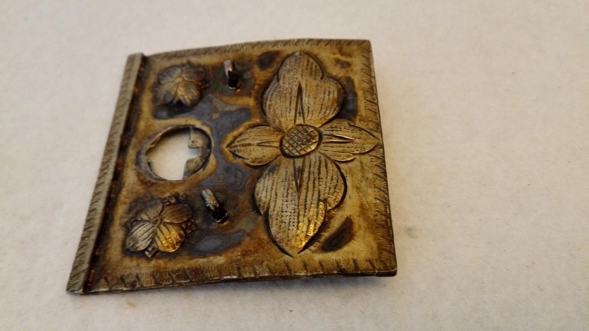 Form: Firkanta. 1 sölvspænde.  Stort firkantet sölvspænde tilhörende et sölvbelte fra Vestreim i Sogndal.  Dette blev i sin tid foræret min svoger dr. Th. Fugelli, der igjen gav det til min söster. Selve stölerne har Fugelli senere beholdt, medens min söster fik spænden. Disse er firkantet 5,4 x 5,2 cm, ustemplete, av sölvblik med pressete blomsterornamenter og paa oversiden forgyldt. Hver spændehalvdel har hat to nedhæng med löv eller medler, der nu mangler.  Gave fra Anna Holmboe, f. Heiberg, Kristiania.
