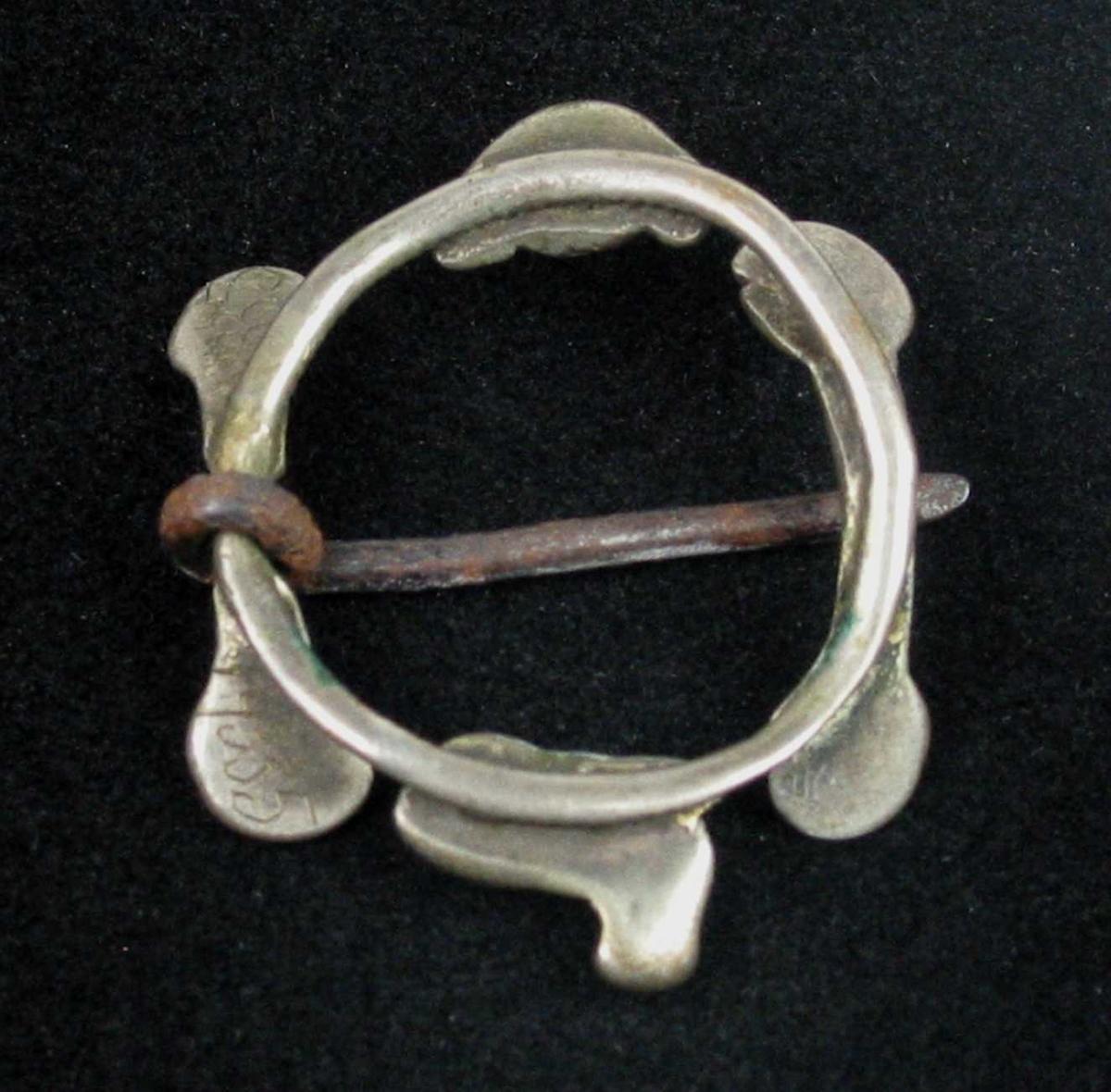 Hornring av sølv med stolper og pålagte figurer. Ringen er skrueformet, men blankslitt på undersiden. De to stolpene har skrueformet midtparti og oppbøyde rosettformede ender. Ringene mellom stolpene har på den ene siden en liggende dyrefigur og på den andre siden en nyreformet rosett. Tornen er av jern.