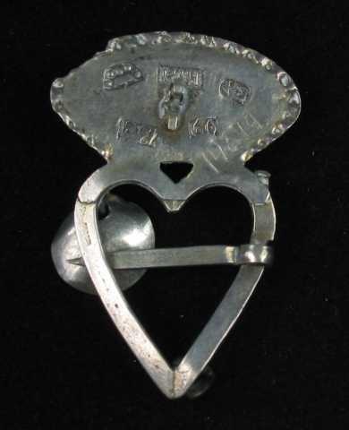 Hjertesprette av sølv med oval krone loddet til hjertet. Krona har tråddekor: fire trådspiraler lagt i s-form, stilt sammen parvis. Mellom disse er det en innfattet rubinrød fasettslipt glassperle (eller stein?) Dette feltet er begrenset av to trådbånd, det innerste av glatt tråd og det ytterste av tvinnetråd. Det er opprinnelig festet tre skåleløv til hjertegrinda, to mangler. Tornen er glatt og er festet på tvers av grinda. Flere stempler på baksida.