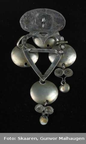 Hjertesprette av sølv med forgylte skåler. Krona er loddet til hjertetgrinda. Den ovale krona er gjordet med tvinnetråd men er ellers glatt.  På midten er det festet en løkke med et skåleløv. Tre like løv er festet til selve grinda. Alle har opprinnelig hatt hjerteformet filigrandekor med løv nederst. To mangler. Grinda er enkel med en påloddet torn på tvers. Nål med kraftig bøyle på baksida (brukket). Flere stempler.