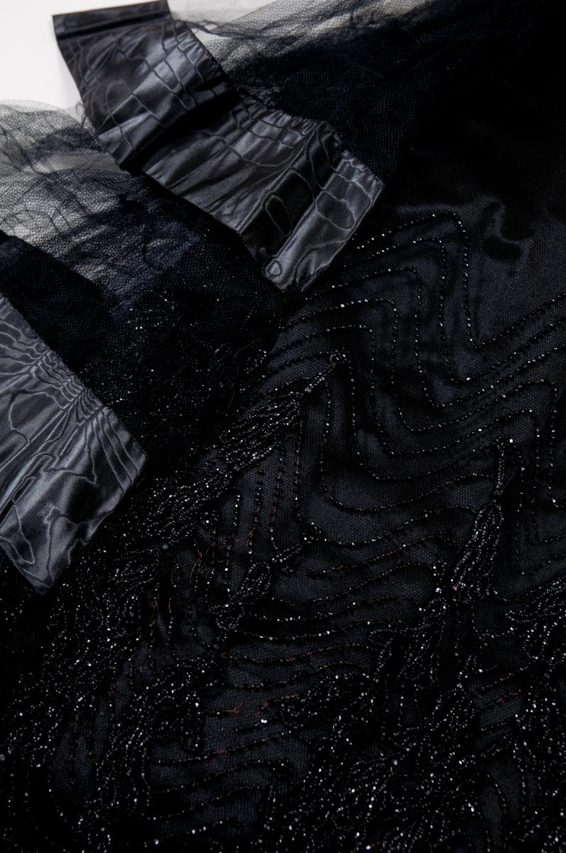 Klänning av svart tyll över svart satin med svarta, hängande pärlbroderier på livet och kjolen. Dekorationsband av moaré i midjan som avslutas med ett spänne med pärldekorationer på höger höft, spännet samlar ihop en siddekoration av tyll som övergår i tre volanger. Volangerna avslutas med ett bredare moaréband. Livet har en markerad rak linje där satinet börjar, hals och axelpartiet är endast fodrat med tyll och och bildar en rund halslinning som är kantad med ett band av satin.