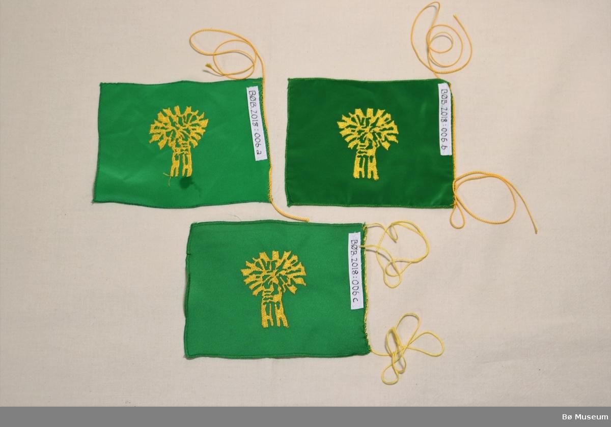 Tre like bordflagg. Logoen til bygdekvinnelaget er brodera midt på kvart av flagga.