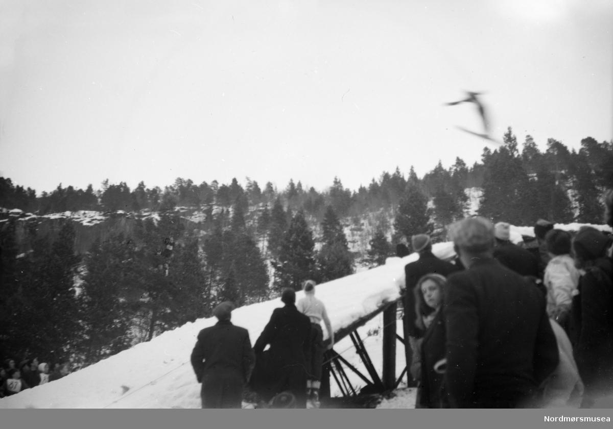 Foto muligens fra et skihoppstevne, trolig på Meisingset i Tingvoll kommune. En fotosamling fra slekten Røv på Meisingset i Tingvoll kommune. Fotografiene kan trolig dateres mellom 1950-1960. Eier av originalmaterialet er Jan Harry Røv. Fra Nordmøre museums fotosamlinger.
