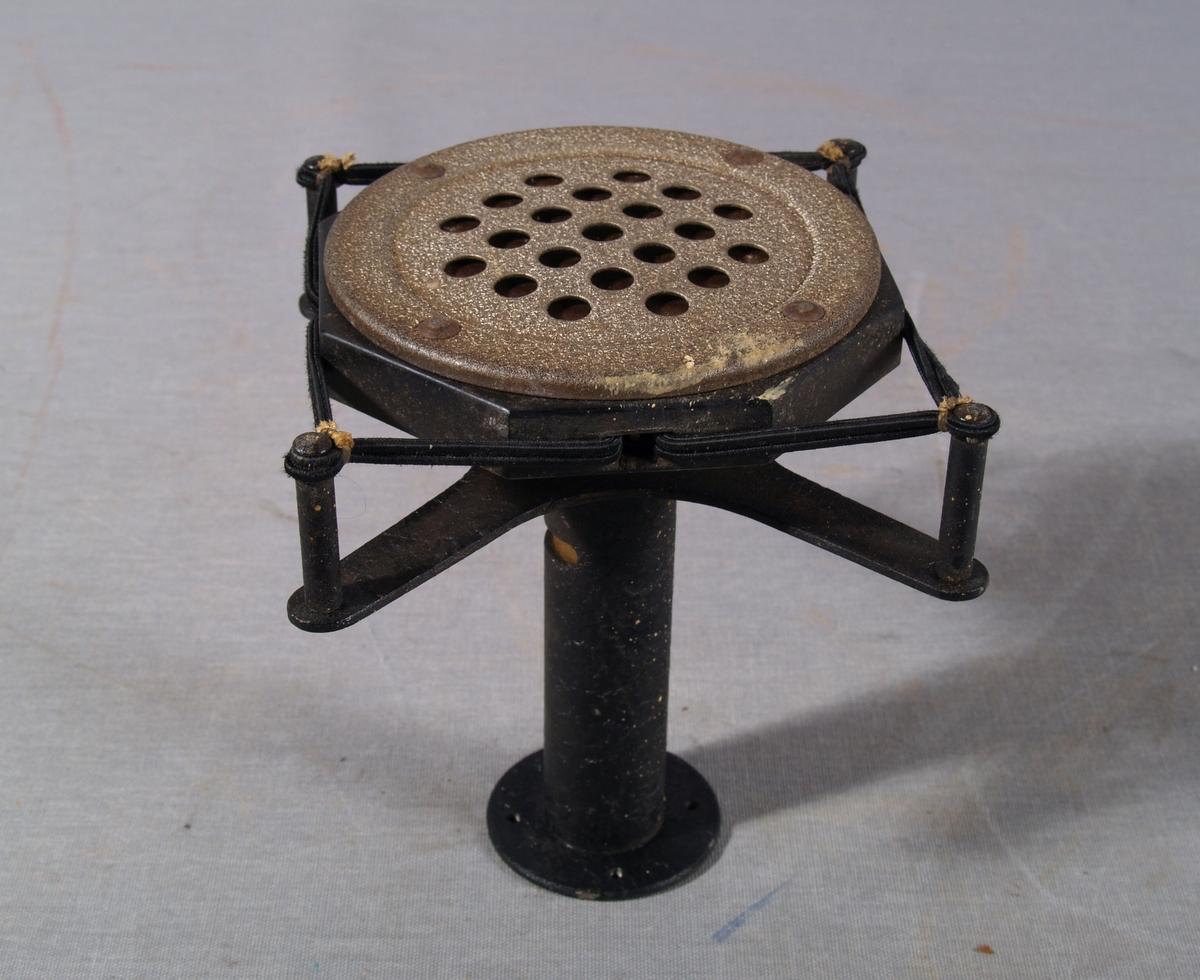 Kullmikrofon for varsling over høyttaler på Brannstasjon. Sirkelrundt mikrofonhode opphengt i elastisk tekstilbelagt feste i fire punkter. Under mikrofonhodet er sylingrisk rør før lydgjennomgang.