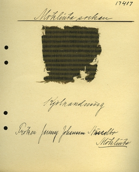 Anmärkningar: Vävnadsprov Olga Anderzons samling. Kjolrandning, Jenny Johansson, Nässelbo Möklinta. Vävprov av halvylle i tuskaft, randigt. Varpen av bomull är i brunt. Inslaget av ull är svart och grönt. L. 810 830 Br. 800 690