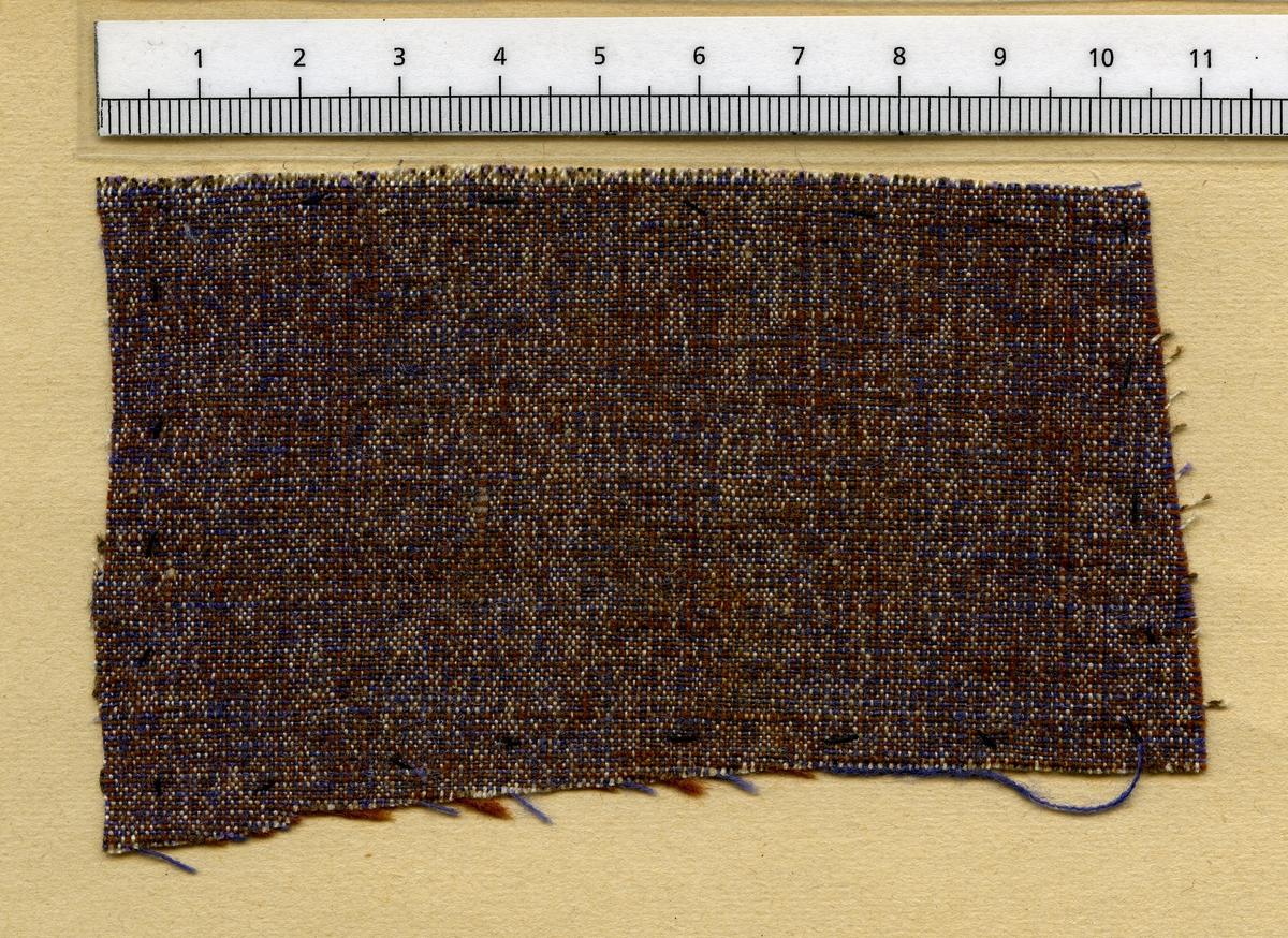 Anmärkningar: Vävnadsprov Olga Anderzons samling. Klänningsväv, Fröken Frida Eriksson, Svensgård Broddbo Sala sn. Vävprov av halvylle i tuskaft, spräckligt. Varpen är randad i vitt, brunt och lila. Inslaget av ull är randat i rödbrunt och lila. L. 660 590 Br. 1090 1080