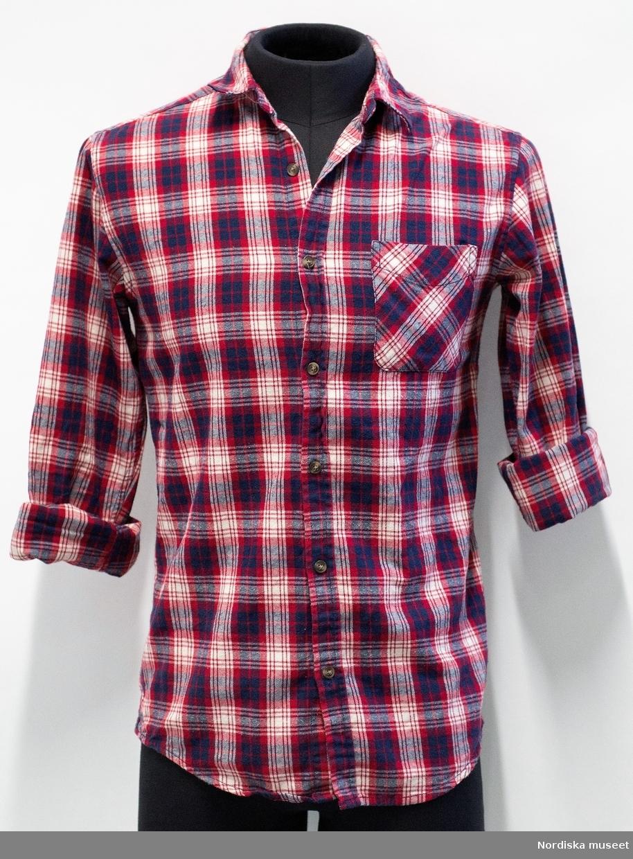 """Skjorta, rutig i blått, rött och vitt. Av 100% bomull i flanell. Krage och lång ärm. Två framstycken med knäppning hela vägen med sju knappar av brun plast. Knapphål på knappslå. Bröstficka på vänster framstycke. Ett bakstycke, ok vid axlarna med hank mitt på oket. Skjortans nederkant något svängd så den är kortare vid sidsömmen. Förstärkning nedtill vid sidsömmen som på vänster sida är försedd med liten broderad fransk lilja (?). Manschett på ärmen med två bruna plastknappar och ett knapphål (för att kunna välja hur tajt manschetten ska sitta runt handleden). Bägge ärmarna uppvikta (Uppvikt 4 varv och uppviket ca 6 cm brett, ärmlängden blir ca 31 cm mätt från ärmsöm på undersidan av ärmen).  På insidan av oket svart etikett med text """"157 / Stab. 1999"""" och storleksangivelse """"S"""". I vänster sidsöm vit etikett med text material- och tvätt-information (se text under """"påförd text"""" nedan) mm. samt två extraknappar.  /Leif Wallin 2017-07-11"""