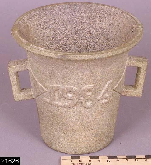 Anmärkningar: Mortel, 1984.  Rund mortel med texten 1984 i relief samt två genombrutna öron. En stöt hör till morteln (se invnr. 21627). Morteln har en rå yta och är sannolikt ej färdigbehandlad. H:135 D:140 Br:155 (avser måttet diameter samt handtagens mått)  Historik: Inköpt tillsammans med invnr. 21626 för 153 kronor plus moms 1983 (en tidigare registrering av f.d. antikvarie Monica Looström gjordes 1983 vilket tyder på att föremålet verkligen har köpts in detta år).