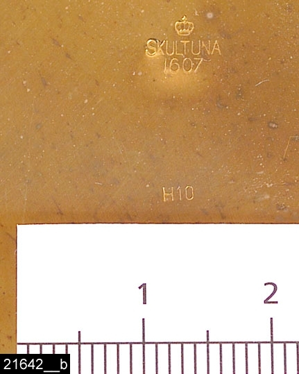 """Anmärkningar: Bunke, 1982.  Rund bunke med snedställda kanter. En upphängningsring på sidan. Invändigt är bunken förtennt. Undertill är den märkt med en krona samt försedd med texten """"SKULTUNA 1607 H10"""" (bild 21642__b), beteckningen H10 betyder att den är tillverkad 1982. Originalkartongen finns bevarad (bild 21642__c). Det är oklart när modellen började och slutade att tillverkas. Enligt en broschyr, utgiven av museet 2007 och benämnd """"Skultunastämplar 1800-2000"""", började den typ av stämpel som finns på föremålet användas 1922. Den användes fortfarande år 2007. H:20 D:90  Tillstånd: Nyskick.  Historik: Inköpt för 32 kronor + moms 1983."""