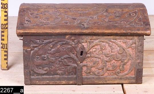 """Anmärkningar: Kista, 1700-tal.  Gångjärnsförsett välvt lock med plattskurna stiliserade ornament (bild 2267__b). Likadana dekorationer som på locket finns på framsidan och sidorna (bild 2267__c-d). På framsidan en nyckelskylt i järn, på sidorna handtag av järn. H:335 B:610 Dj:440  Hela kistan ger ett brunrödmålat intryck, den är dock randigt målad med omväxlande brun och svart färg (bild 2267__d). Denna färg är gammal (1700-tal), men ej ursprunglig. Den rosaaktiga originalfärgen syns på flera ställen. Invändigt är kistan odekorerad och omålad, förutom insidan av locket som är brunrödmålat.  Tillstånd: Ett järnbeslag på framsidan saknas. Detta har löpt till locket och fungerat som en låsmekanism. Nyckel saknas till låset. Det ena gångjärnet till locket är trasigt.  Historik: Enligt liggaren är föremålet inköpt """"genom intendent på auktion vid Carlsberg."""""""