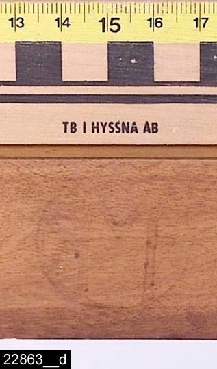 """Anmärkningar: Stol, 1900-talets första hälft.  Svagt konvext överstycke. Svagt svängda bakstolpar. Genombruten rygg med en ryggslå med skuren dekor (bild 22863__c). Löstagbar stoppad sits med blårandigt tygöverdrag. På insidan av vänster sarg finns märkningen SMF (bild 22863__d). Märket står sannolikt för Svenska möbelfabriken Bodafors. S-svängda framben. Samtliga ben är utåtsvängda från stolen (bild 22863__b). H:845 Br:450 Dj:410  Se även invnr. 22862.  Historik: Inköpt till utställningen """"Bostad"""" hösten 1985 från Fastberg & Söner, Vångsta, Västerås för 125 kronor."""