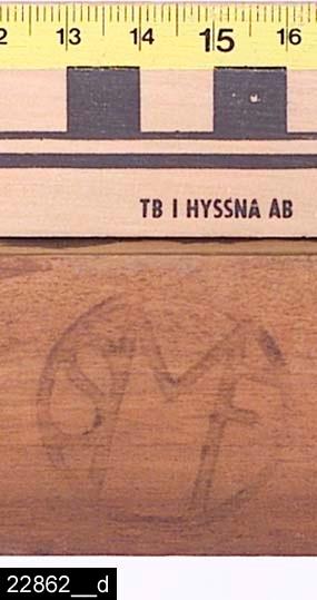 """Anmärkningar: Stol, 1900-talets första hälft.  Svagt konvext överstycke. Svagt svängda bakstolpar. Genombruten rygg med en ryggslå med skuren dekor (bild 22862__c). Löstagbar stoppad sits med randigt tyg. På insidan av vänster sarg finns märkningen SMF (bild 22862__d). Märket står sannolikt för Svenska möbelfabriken Bodafors. S-svängda framben. Samtliga ben är utåtsvängda från stolen (bild 22862__b). H:840 Br:450 Dj:490  Se även invnr. 22863.  Historik: Inköpt till utställningen """"Bostad"""" hösten 1985 från Fastberg & Söner, Vångsta, Västerås för 125 kronor."""