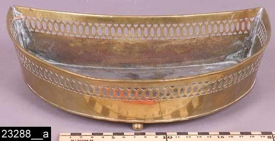 """Anmärkningar: Spottlåda, 1830-1850-tal.  Halvmåneformad spottlåda med genombruten dekor i kanterna. I botten finns stämplarna """"S:B 2"""" (bild 23288__b). Spottlådan står på tre kulfötter. Enligt en broschyr, utgiven av museet 2007 och benämnd """"Skultunastämplar 1800-2000"""", användes den typ av stämpel som finns på föremålet under 1830-1850-talen. Snarlika spottlådor finns nämnda och avbildade i priskuranter från Skultuna under hela 1800-talet. Modellen tycks inte nämnvärt ha ändrats under detta sekel. H:65 L:270 Dj:175  Tillstånd: En lagning i ena hörnet. Små bucklor på ett flertal ställen.  Historik: Gåva från Berit Blissinger, Klockartorpsgatan 15, Västerås, 1988."""