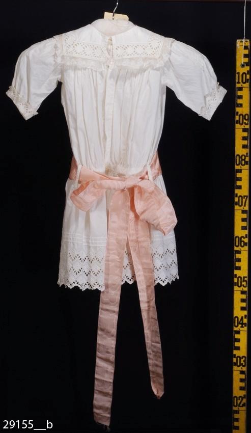 Anmärkningar: Irsta sn Gäddeholm Barnklänning som tillhört Ulrika Lewenhaupt 1856 - 1946, gift Hamilton.  Barnklänning av vitt bomullstyg med ärmar, krage, rynkad kjol, underklänning och skärp. Klänningen har vertikala infällda brodyrband, brydyr runt klänningsfållen, på kragen och runt de 3/4-långa ärmarna. Den rektangulära kragen är ytterst kantad med brysselspets. Klänningen knäpps i ryggen med sex knappar. Alla finns.  Kring midjan knyts ett långt ljust laxrosa skärp av siden. Längd 2640 mm, bredd 60 mm.  Underklänningen av vitt bomullstyg (540 mm lång) är kantad runt halsen och kjolkanten med band av brodyr. Klänningen märkt E.L. Knäpps med tre vita knappar i ryggen, varav den översta saknas. Några få nötningshål på nedre delen av kjolen bak.