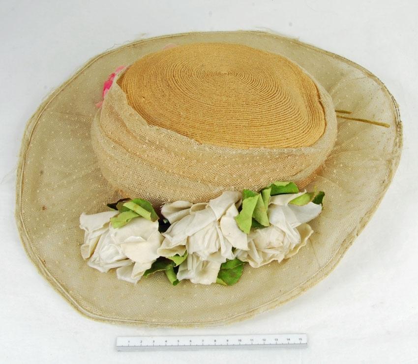 Anmärkningar: Irsta sn Geddeholm Har tillhört Ewa Beck Friis gift Lewenhaupt född 1856 död 1940  Hatt, 1 st, damhatt av halm ? Hattkullen försedd med brett band av beig tyll med prickar, liksom det breda runda hattbrättet, som har en båge av metall. På motstående sidor av hattkullen en kvist med tre vita rosor med gröna blad och tre kvistar med rosa rosor och gröna blad. Hattkullen är även invändigt fodrad med beig tyll.