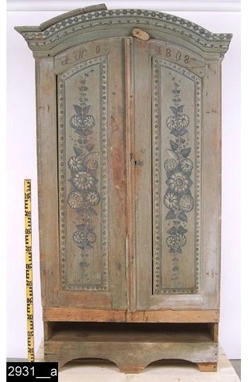 """Anmärkningar: Dubbelskåp, grönmålat, s.k. tunamåleri, målad datering 1808  Framskjutande rundat krön med målad blomdekor (delvis stämpelmålad dekor) i mörkgrönt och vitt. Spegelförsedda pardörrar med avfasade profilerade kanter. Färgen på dörrarna bär spår av naturligt slitage. Speglar med falsk gering och målade blomstermotiv i mörkgrönt och vitt. Speglarna omramas av stämpelmålad dekor. Målat med mörkröd färg i dörrarnas ovankant """"A N O 1808"""". Dörrhasp i trä och nyckelskylt i mässing (bild 2931__b). Plats för draglåda under dörrar. Kontursågat underrede framtill. Invändigt skedhylla och tre hyllplan. Lås, hasp och ögla i järn. H:2050 Br:1165 Dj:425.  Sannolikt är skåpet målat av en dalmålare från Tuna socken i Dalarna. Dessa utmärkte sig för att arbeta i en blå färgskala samt mer figurativt och naturalistiskt än andra dalmålare, vilka arbetade med många färger och dessutom mer abstrakt (kurbits).  Tillstånd: Delar av krön saknas. Dråglåda saknas. Underrede skadat och till stora delar utbytt. Lagning med järn och spik på insidan av höger dörr.  Historik: Köpt av Larsson, Råby, Kungsåra sn, 1923.  Tidigare felmärkt med inv.nr 2930."""