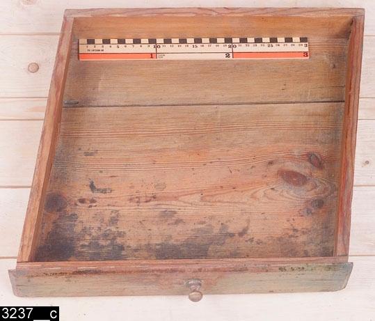 Anmärkningar: Bordsstol, omkring 1800.  Rakt överstycke som är profilerat i nederkanten. S-formade bakstolpar som är profilerade i innerkanterna. Genombruten rygg med sju spjälor. Spjälorna är fästa i en ryggslå, som är profilerad i överkanten. Gångjärnsförsedd sits av trä som går att fälla ut och då får man ett bord (bild 3237__b). Undertill finns en grind med profilsvarvade ben som går att dra ut, bordsskivan skall vila på grinden. På höger sida finns en romboid draglåda med svarvad knopp och spår av bläck inuti (bild 3237__c). Vänster sidosargar och baksargen är profilerade i nederkanterna. Profilsvarvade framben med svagt konformiga fotavslutningar. Ett H-kryss binder samman benen. H:855 Br:655 L:1010 Dj:520  Djupet avser måttet mellan ryggen och långsidan av sitsen mot betraktaren. Längden avser samma mått men när sitsen är utfälld (bordsstolen är vänd 90 grader åt höger på bild 3237__b då sitsen är utfälld).  Hela bordsstolen är av ljust lövträ utom sitsen/bordsskivan och draglådan som är av furu. Hela bordsstolen är gråmålad och bär spår av naturligt slitage. Både sitsen och bordsskivan är kraftigt nötta vilket vittnar om att man verkligen använt bordsstolen som både bord och stol.  Historik: Bordsstolen har tillhört en skomakare (dock oklart under vilken tid den tillhört skomakaren). Köpt av Axel Andersson, Hebo, Västerfärnebo sn.  Negativnummer B-5435