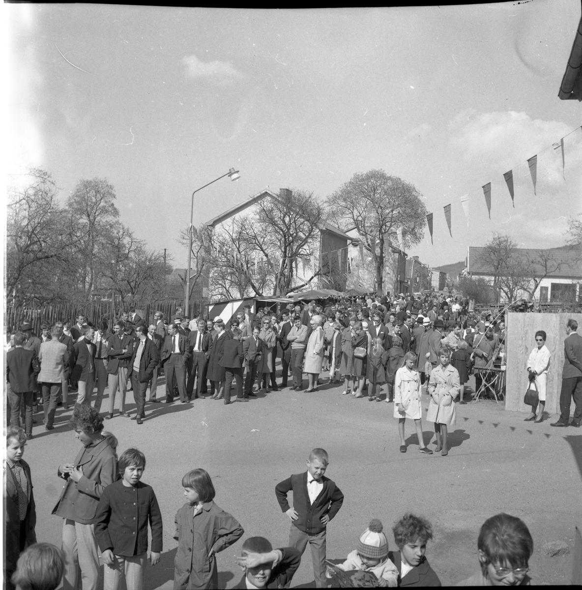 Lions vårmarknad 1964. Barn och vuxna samlade på Sjögatans södra del, nedanför Hallska gården. I folksamlingen finns bland andra Daniel Björk, Gunilla och Lars Rundqvist (han har ljus tröja och hon är blond med ljus kappa.