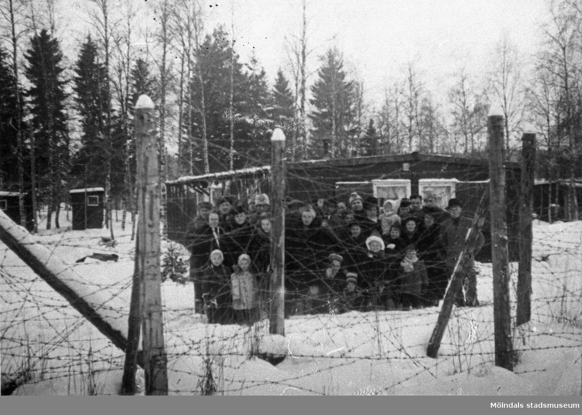 """Familjerna står bakom en taggtråd som omringar det så kallade karantänlägret i Byringe, Örnsköldsvik. I lägren avlusades flyktingarna och de läkarundersöktes grundligt. Deras kläder och tillhörigheter brändes. Vid minsta sårbildning eller spricka i huden fördes flyktingarna till sjukhus. Rädslan för smittsamma sjukdomar var stor under rådande krig. Hösten 1944 flydde 32.000 estländare från kriget i Estland till Sverige. Ett sextiotal personer tog jobb på August Werners textilfabrik i Lindome. Kvinnorna arbetade i spinneriet och männen i färgeriet. Mer information finns i uppsatsen """"Estländska textilarbetare i Lindome"""" som finns i Mölndals stadsmuseums interna arkiv."""