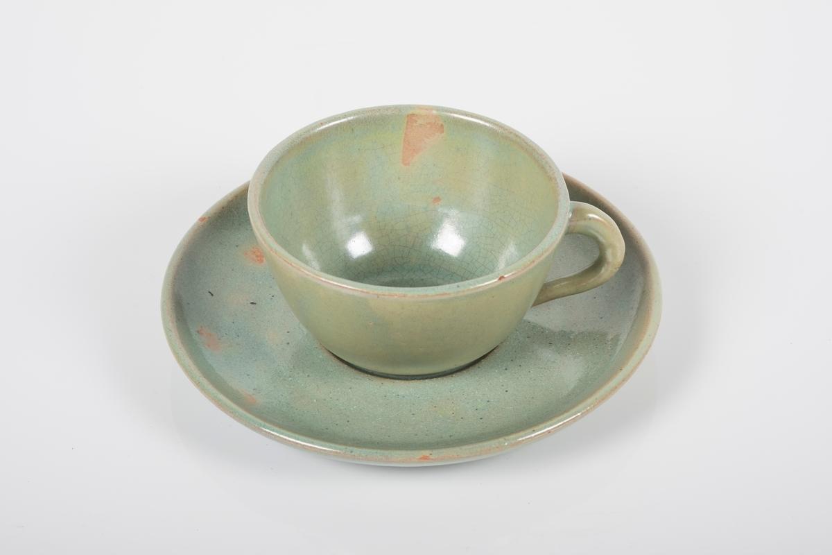 Kopp med skål i keramikk med grønn lasur. Buet hank på koppen. Skålen har spor etter tre knotter på bunnen, usikker funksjon. Bunnen på koppen og skålen har matt overflate.