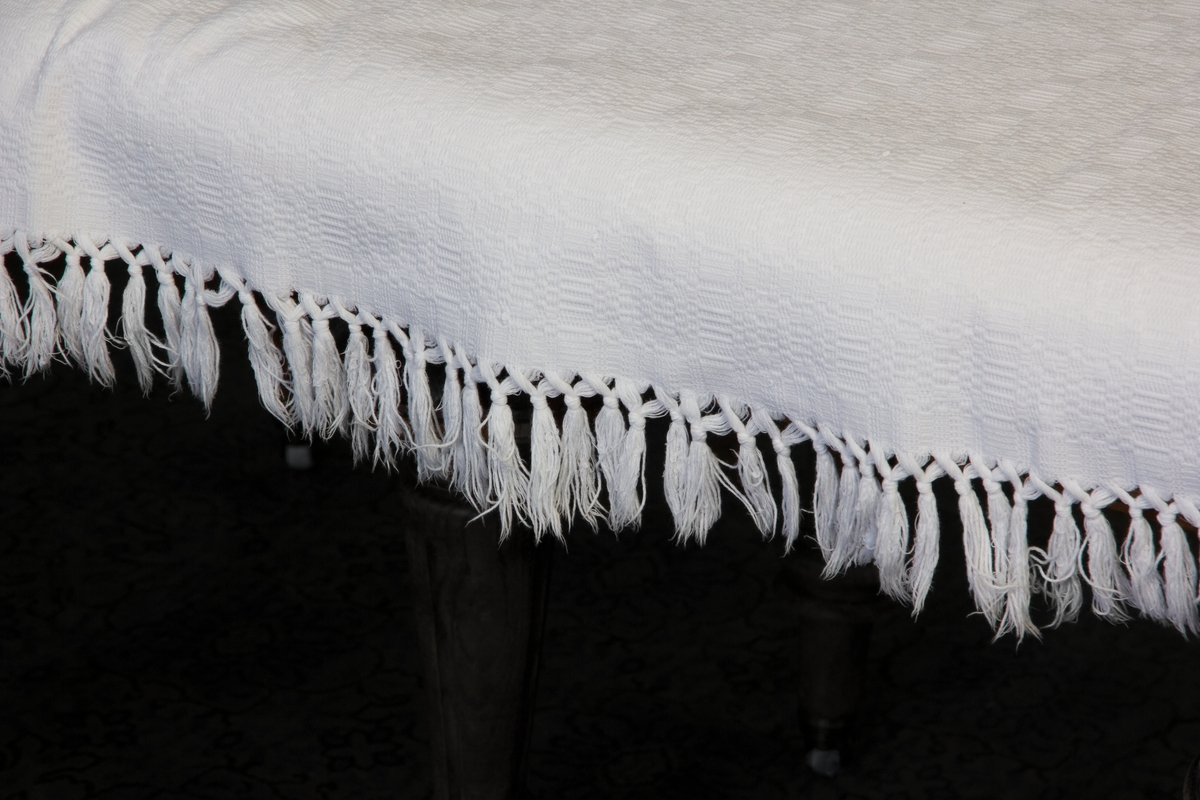 Sängöverkast eller duk av maskinvävd, vit, mönstrad bomull. Frans på fyra sidor. Hopsytt av två våder.