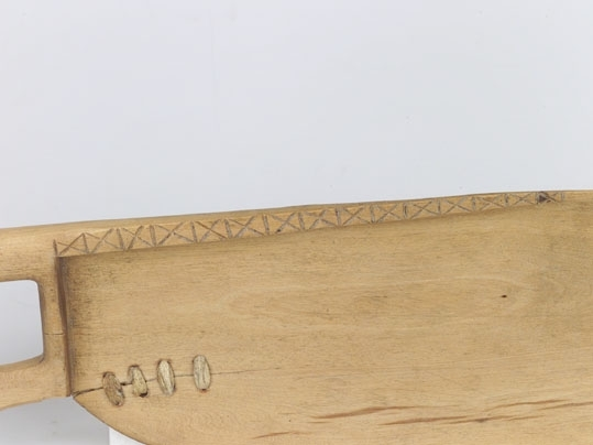 Anmärkningar: Skäktkniv av trä. Rakt handtag. Skyddet svagt V-format längs bladets övre kant löper en list med X-dekor inskuren. Bladets kant prof. Bladet på ett ställe lagat, sydd med sentråd. 4 stygn.L.  450 St. Br. 120