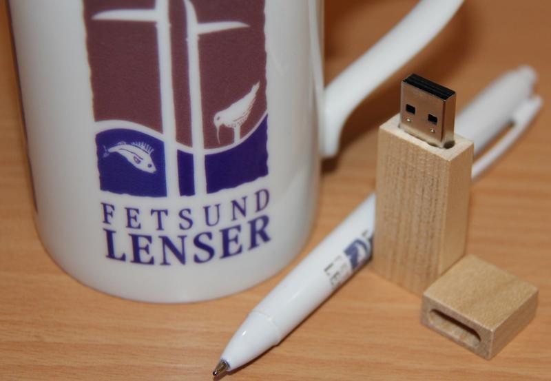 Nærfoto av lensekopp, penn og minnepinne - alt med Fetsund lenser logo