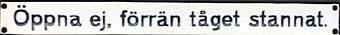 Långsmal rektangulär skylt av emaljerad plåt med blå text på vit botten. Text: Öppna ej, förrän tåget stannat.  Anmrkning: Jämför med Jvm 11701 och Jvm 11558 (ålderdomligare och med andra mått). Snarlik är Jvm 11555 ( brun text, ej blå). Samma mått och typsnitt.