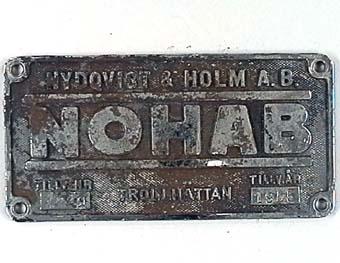 SRektangulär skylt av förnicklad mässing med text i relief mot gråsvart, räfflad botten. Från elloket SJ Da 883. NOHAB tillv nr. 2249.