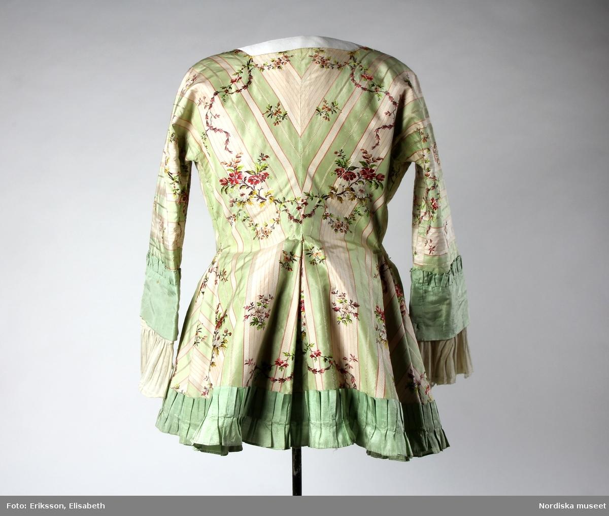 Katalogkort: Kofta 1780-talet för fru J.Keyser f. Halling 1751-1797, gift 1770. Av bredrandig vit och ljusgrön taft med smala röda linjer samt glesa, slingrande blomrankor i färger. Helt fodrad med ljusrött glättat linnetyg. Koftan består endast av två stycken ( halva ryggen, ärmen och motsvarande stycke i ett, utan axelsöm, endast ryggsöm och sidsöm som övergår i ärmens innersöm.) hopknuten med rosetter kant i kant mitt fram med tre par breda ljusgröna sidenband. Kanten nedtill rundskuren med inlagda veck i rygg och sidor samt kilar i framstyckena. Ett veckat rysch av ljusgrön taft är påsytt runt kanten nedtill från den nedersta rosetten. Ärmen går över armbågen med bred manschett av ljusgrön taft med smalt veckat rysch i överkanten. Rynkade enkla engageanter av glest, vitt, randat linnetyg med smal knypplad spets i kanten. Obetydligt lagad å ärmarna. Byst 90 cm, midja 80 cm. Tygets vådbredd minst 56 cm, tygåtgång vid denna bredd 2,55 m.