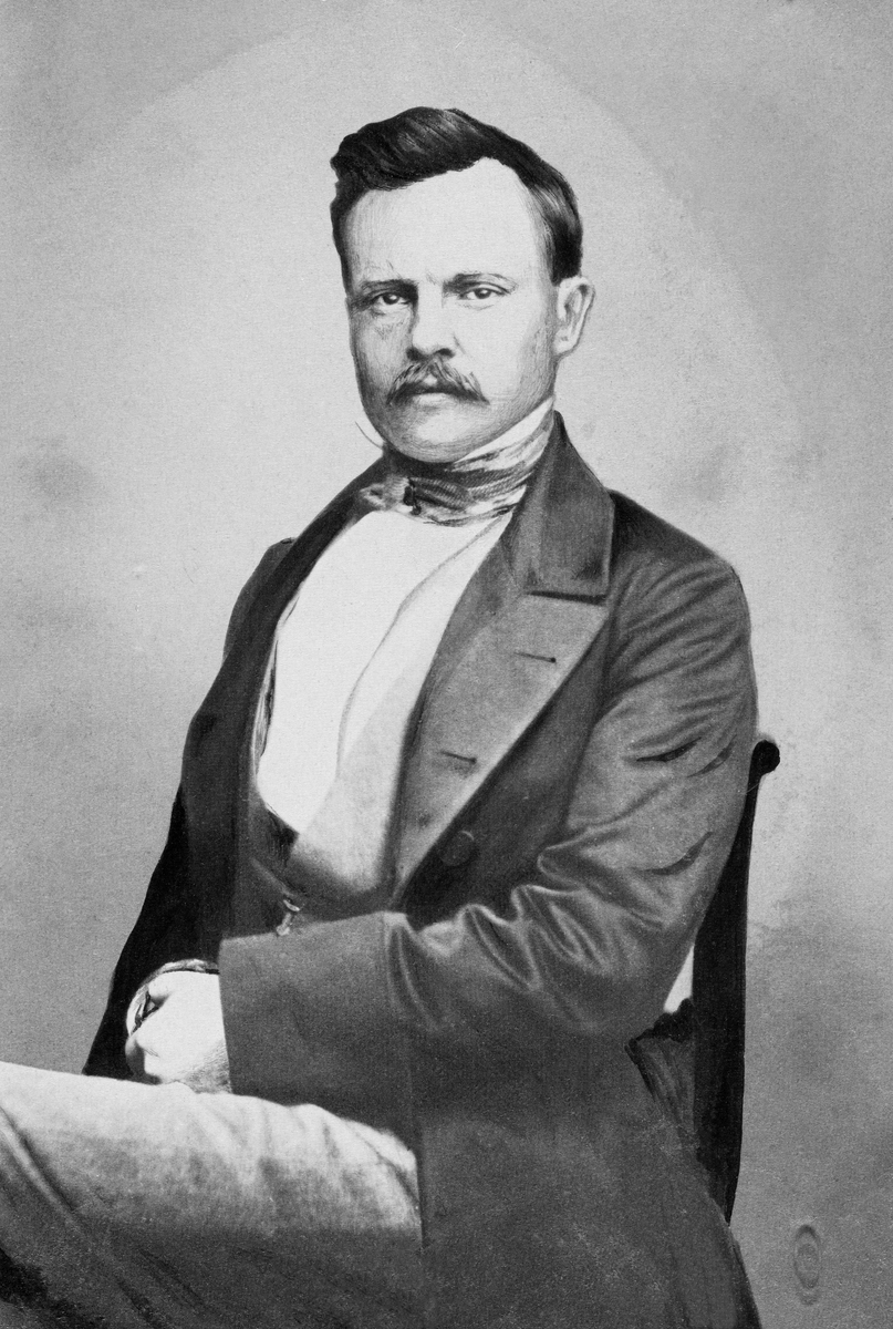 Fotografisk portrett av den tyske forstmannen Friederich Casimir Gustav Heyer (1826-1883), vanligvis bare omtalt som Gustav Heyer. Han er avbildet sittende på en stol i et fotografisk studio.  Heyer var kledd i ei lang, frakkeliknende jakke med store slag, med vest og kvit skjorte under.  Om hanlsen har han knyttet et silketørkle.  Da dette fotografiet ble tatt var den kjente forstmannen antakelig i 30-40-åra.  Han hadde bart og skrått bakoverstrøket, mørkt hår.    Gustav Heyer var sønn av Karl Heyer, som var professor ved det kjente skogakademiet i Giessen i den tyske delstaten Hessen.  Han gikk på gymnas hjembyen, og etter at han hadde tatt artium satt han åtte semestre under (1843-1847) under farens kateter.  Deretter reiste han ut og praktiserte et par år, før han vendte tilbake til Giessen i 1849-1850.  Der var han først «privatdosent» en periode, inntil han i 1853 ble utnevnt til professor med forvaltningsansvar for skogene i området.  Med de erfaringene dette gav ham fikk han også undervisninsplikt i praktisk skogbehandling.  Gustav Heyer gjorde seg bemerket som en dyktig fagmann, og han skal ha blitt tilbudt professorater både i Zürich og Karlsruhe, tilbud han avslo, angivelig fordi han var så sterkt knyttet til hjemtraktene.  I 1868 sa han derimot ja til et tilbud om å bli direktør for det prøysiske forstakademiet i Münden, et embete som gav høyere lønn, samtidig som Heyer visste at det forstinstituttet i Giessen var truet av omorganiseringer.  I 1875 skal han ha søkt et professorat ved den østerrikske «Hochschule für Bodenkultur», en stilling Heyer ikke fikk.  Etter dette skal han ha bestemt seg for å bli i Tyskland.  Som skogakademiker skal Gustav Heyer ha gjort seg bemerket med uvanlig bred naturfaglig innsikt, og som en klartenkt fagmann som visste å formidle sin faglige kompetanse så vel muntlig som skriftlig. Hans egen forskning var først og fremst knyttet til det skogøkonomiske fagfeltet, men han underviste og skrev også med suksess i mer produksjons