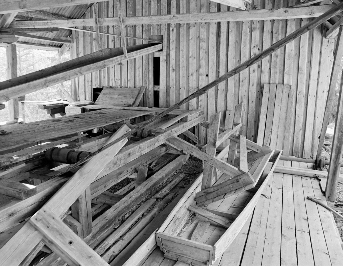 Interiør fra Mastveltsaga i Åsnes.  Fotografiet er sommeren 1975, da lokomobilen som drev saga og den øvrige innredningen ble demontert og flyttet til et nytt saghus på Norsk Skogbruksmuseum (Norsk Skogmuseum) i Elverum.  Saghuset på Mastvelta var en bindingsverkskonstruksjon, som i den ene enden var kledd med over- og underliggende panel av vankantete bord, mens sagbenken sto i den delen av bygningen som ikke hadde bordkledde vegger.  Dette fotografiet er tatt fra området ved sagbenken mot det innkledde rommet, der lokomobilen som drev saga var plassert.  Da dette fotografiet ble tatt var saginteriøret preget av at det var lenge siden anlegget hadde vært i drift.  Det lå blant annet et bord og ei treramme på golvet. Trongaardsaga. Lokomobilsag.  Mer informasjon om Mastveltsaga og om lokomobilsager generelt finnes under fanen «Opplysninger».